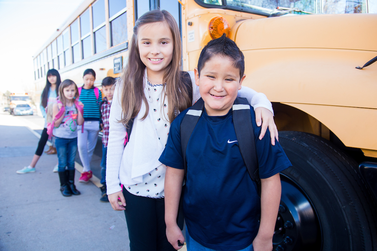 students standing in front of a school bus