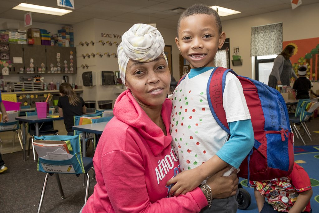 A parent hugs a child in a classroom.