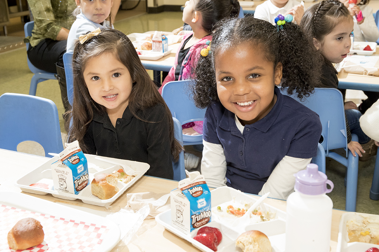 Students eat lunch in a cafeteria.