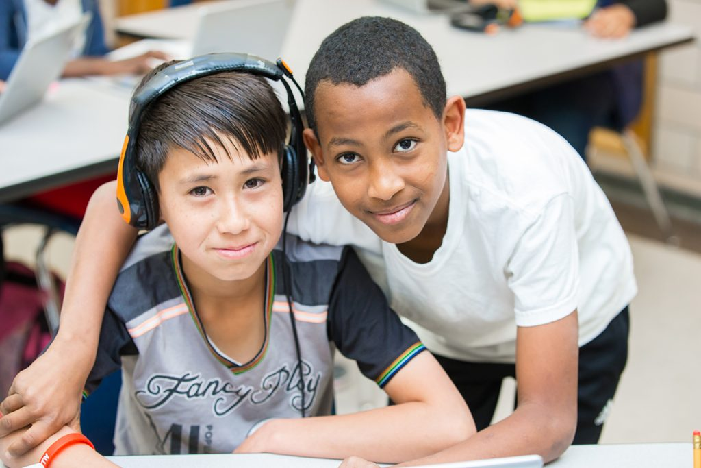 Students use headphones in a classroom.